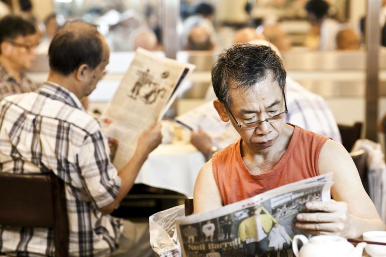 港式茶樓文化少不了嘆報紙一環,今日的信興酒樓傳統依舊,人人低頭讀報,而不是看手機。